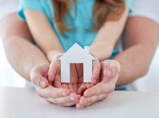 close up of man and girl hands with paper house