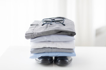 close up of folded male shirts and shoes on table
