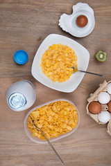 Cornflakes with milk, eggs,  on a wooden brown background