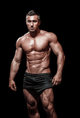 very muscular handsome athletic man on black background, naked t