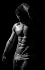 black and white studio shoot of strong athletic man on dark back