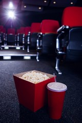 Empty rows of red seats with pop corn and drink on the floor