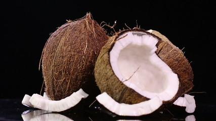 Fresh coconuts on black background in rotation move