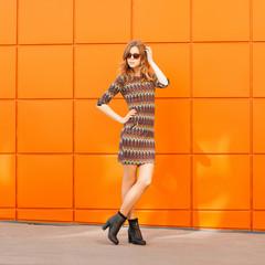 Pretty fashion woman in dress and sunglasses.Background of a bri