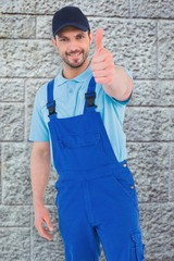 Composite image of repairman gesturing thumbs up
