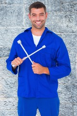 Composite image of smiling male mechanic holding lug wrench