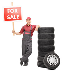 Mechanic standing by a pile of tires and holding for sale sign