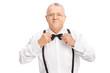 Elegant senior gentleman adjusting his bow-tie