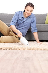 Man cleaning carpet with a handheld vacuum cleaner