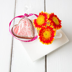 Cup full of pink gerbera  flowers and  heart shape cookie