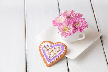 Cup full of pink  mum flowers and  heart shape cookie on white w