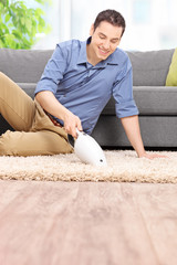 Man cleaning his carpet with a handheld vacuum cleaner