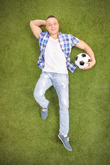 Casual man lying on a field and holding football