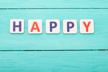 Word happy on blue wooden background