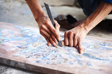 Vietnamese craftsman carving out and painting a floral pattern