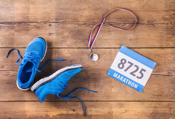 Running shoes, medal and race number on a wooden background