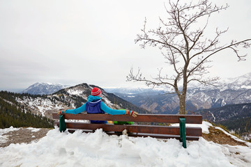 Girl resting on bench on top