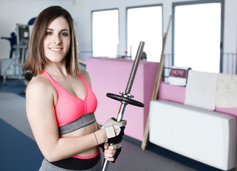 Strong woman weightlifting at the gym looking happy