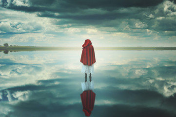 Red hooded woman in a strange landscape with clouds
