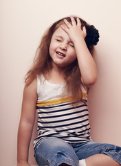 Disappointed kid girl thinking with hand on the head. Portrait