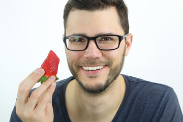happy young man eating a strawberry