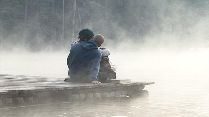 Young Lovers in the lake during morning foggy sunrise