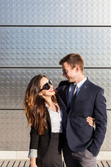 Happy Business Couple Hugging in a Sunny Day Against a Metallic