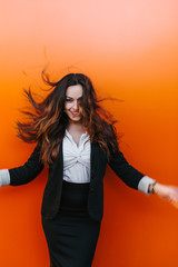 Happy Businesswoman Against an Orange Wall
