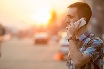 Young man making call with smartphone on sunny street