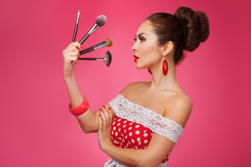 Woman with makeup brushes.   She is standing against a pink