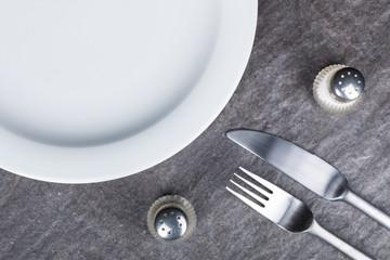 Teller mit Besteck und Gewürzstreuer auf Steinplatte