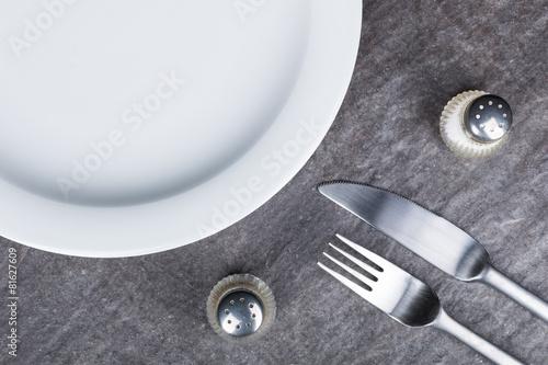 Teller mit Besteck und Gewürzstreuer auf Steinplatte - 81627609