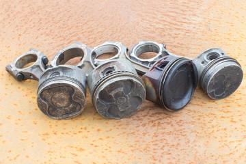 Four various piston rods lie on rusty metal