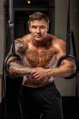 Muscular guy with tattos in a gym