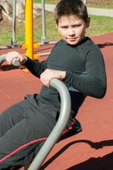 The boy on outdoor sport ground / gym