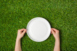 Human hands holding empty paper plate on grass - 81630416