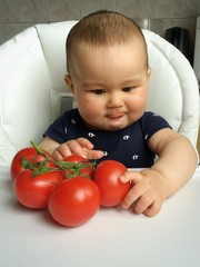baby with tomato at kitchen