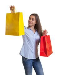 Frau mit braunen Haaren zeigt Einkaufstaschen