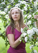 young attractive woman standing near blossoming apple tree...