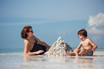 Young mother and her little son building sand castle at beach