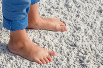 Close up of child feet on a tropical sandy beach, Florida