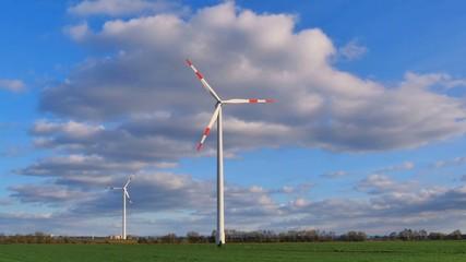 Windräder in Landschaft mit Wiese und Himmel
