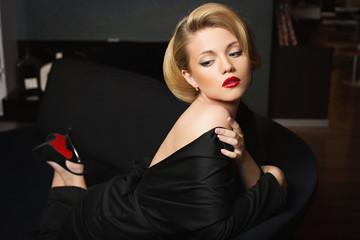 Beautiful young woman wearing black gown lying on sofa