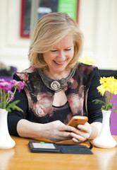 Mature blonde woman reads the message on the phone while sitting