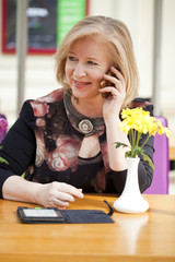 Mature beautiful woman is calling on a cell phone while sitting