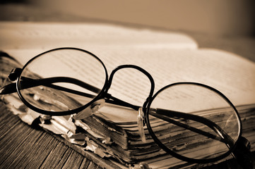 round-framed eyeglasses and old book, in sepia toning