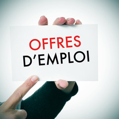 woman with a signboard with the text offres d'emploi, jobs in fr
