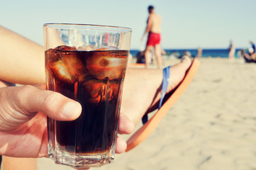 young man hanging out on the beach with a cola drink