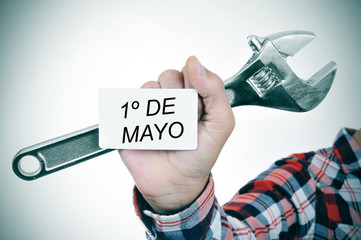 man with adjustable wrench and signboard with text 1o de mayo, m