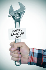 man with adjustable wrench and signboard with text happy labour